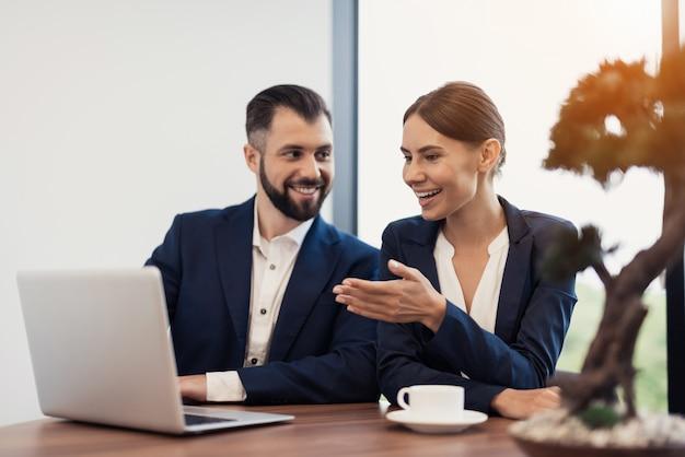 Un uomo e una donna in tailleur rigorosi in ufficio