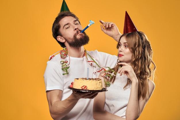 Un uomo e una donna per un compleanno con un cupcake e una candela in un cappello festivo si divertono e celebrano la vacanza insieme, coppia felice