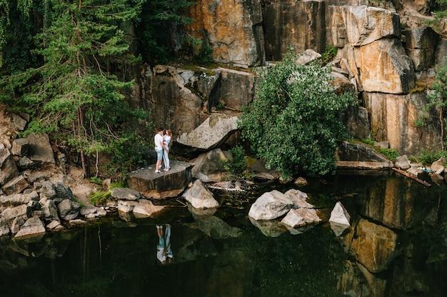 Un uomo e una donna si alzano e si abbracciano sulle rocce