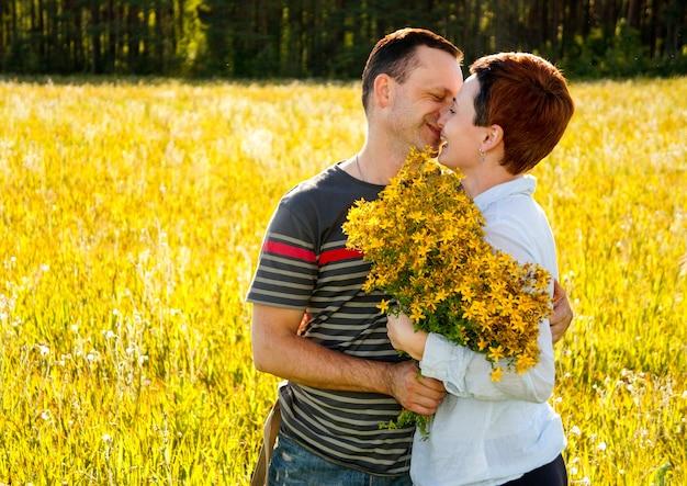 Un uomo e una donna si baciano, campo di fiori gialli, concetto di amore, concetto di famiglia