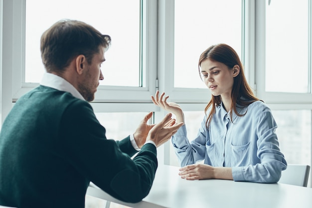 Un uomo e una donna sono seduti a un tavolo a discutere, litigare tra loro, un vero litigio, questioni familiari