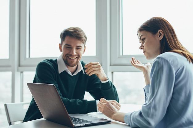 Un uomo e una donna sono seduti a un tavolo davanti a un computer portatile a parlare di lavoro