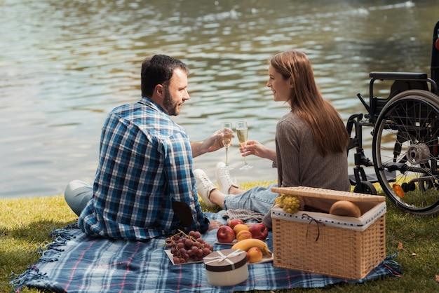 Un uomo e una donna sono seduti sulla riva del lago