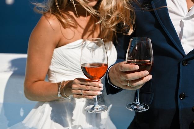 Un uomo e una donna sposi tengono bicchieri di vino e celebrano il loro matrimonio contro il cielo blu e il mare