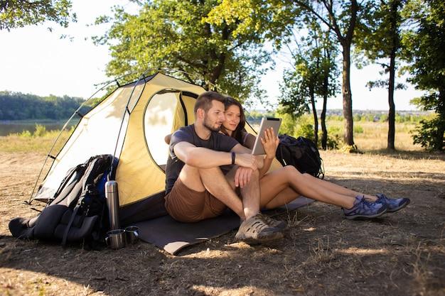 Un uomo e una donna vicino alla tenda con un tablet. parlano di comunicazione video con gli amici