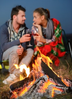 Un uomo e una ragazza bevono vino sotto un romantico falò.