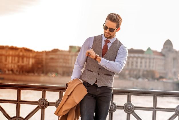 Un uomo elegante in piedi accanto a un fiume e controllando l'ora