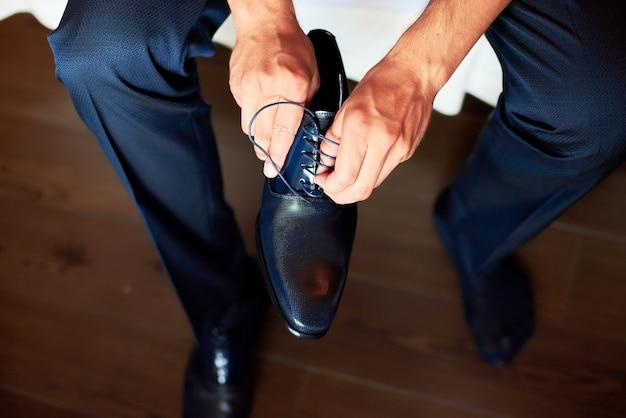 Un uomo elegante indossa scarpe nere, in pelle e formali. legare le scarpe.