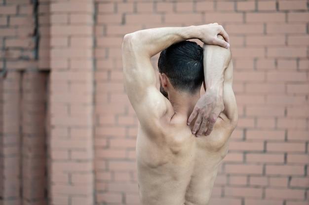 Un uomo fa un riscaldamento prima di allenarsi in strada. allenamento, allenamento, stile di vita