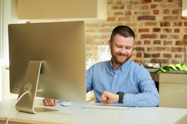 Un uomo felice con la barba che guarda l'orologio da polso durante un video briefing online con i suoi colleghi a casa