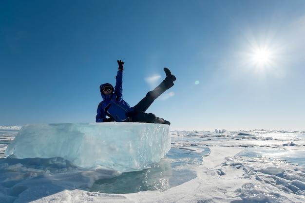 Un uomo felice giace su un blocco di ghiaccio contro un cielo blu in inverno
