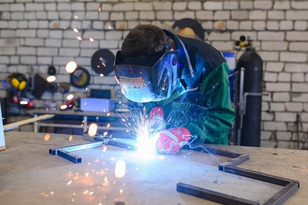 Un uomo forte è un saldatore in una maschera per saldatura e pelli per saldatori, un prodotto metallico viene saldato con una saldatrice in garage, scintille blu volano ai lati