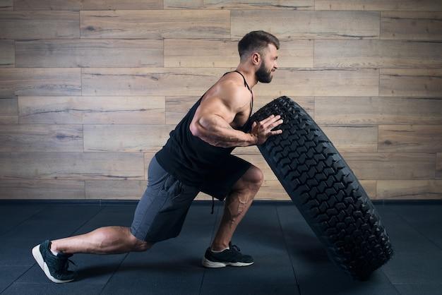Un uomo forte in canottiera nera e pantaloncini grigi con la barba cerca di spingere una gomma in una palestra