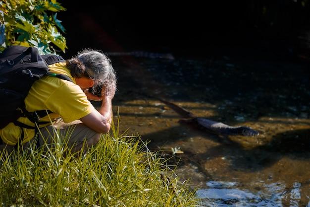 Un uomo fotografa una grande iguana in un viaggio lungo il fiume.