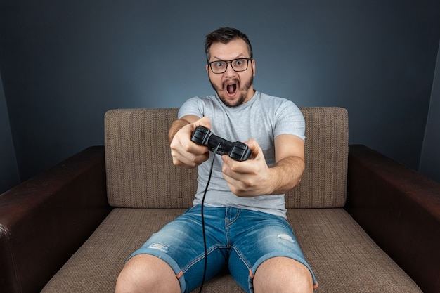 Un uomo gioca alla console, i videogiochi reagiscono fortemente ed emotivamente mentre sono seduti sul divano. giorno libero, divertimento, svago.