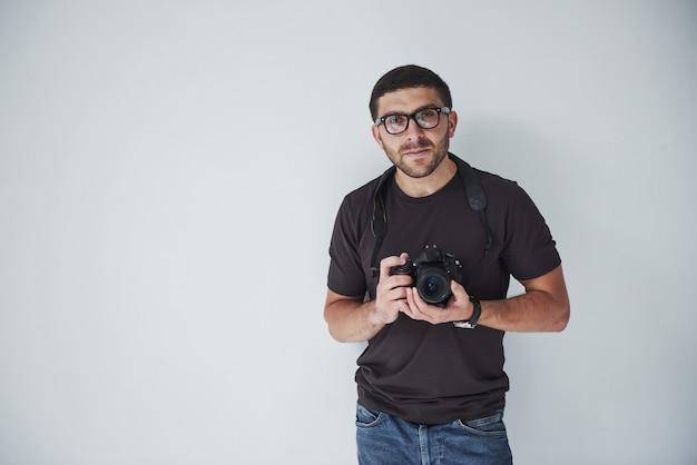 Un uomo giovane hipster in oculari detiene una fotocamera dslr nelle mani in piedi contro un muro bianco