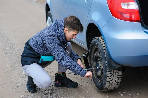 Un uomo ha rotto una ruota su un'auto e la cambia da sola sulla strada.