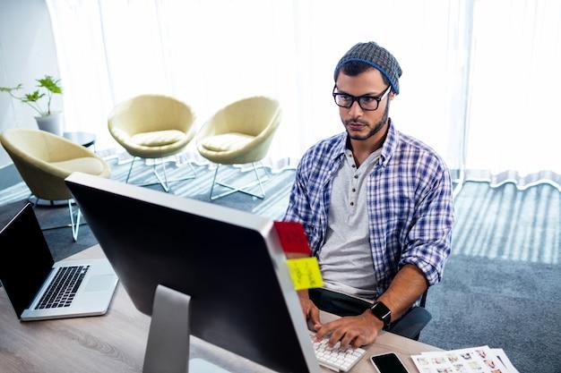 Un uomo hipster lavorando alla scrivania del computer