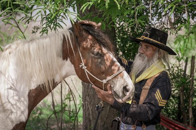 Un uomo in abito da cowboy con il suo cavallo
