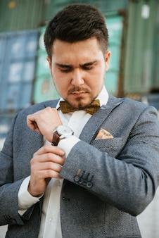Un uomo in abito grigio posa per strada per pubblicizzare abiti da uomo. riprese per negozio di abbigliamento maschile
