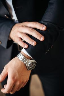 Un uomo in abito nero e camicia bianca posa in casa per pubblicizzare l'abbigliamento maschile. riprese per negozio di abbigliamento maschile