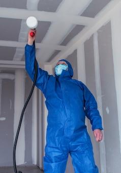 Un uomo in abito speciale dipinge le pareti con una pistola a spruzzo, dipingendo pareti e soffitti