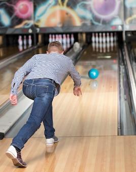 Un uomo in bowling lancia la palla nei birilli.