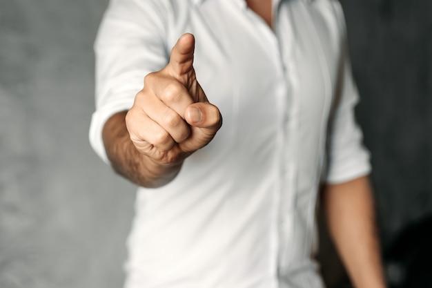 Un uomo in camicia bianca su cemento grigio spinge il dito indice