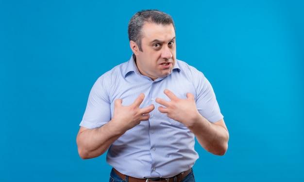 Un uomo in camicia blu mostra emotivamente aggressività e rabbia con le mani rivolte a se stesso su uno spazio blu
