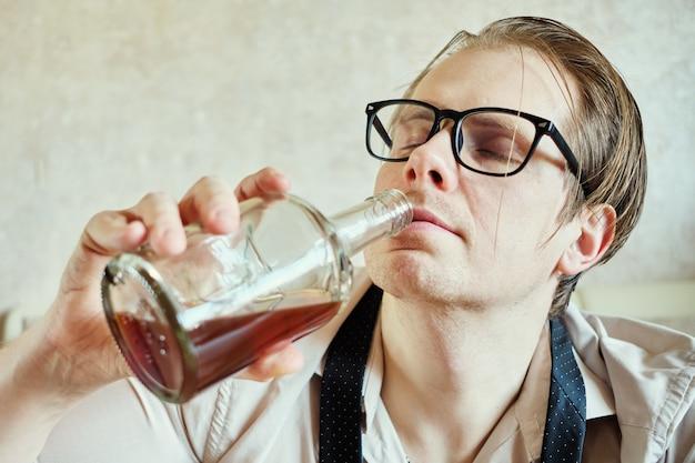 Un uomo in camicia e cravatta beve cognac da una bottiglia