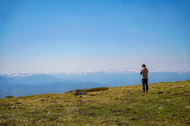 Un uomo in felpa con cappuccio staning davanti a sfondo di montagne