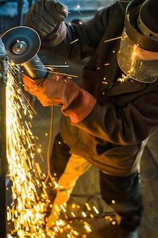 Un uomo in forma di lavoro e una maschera taglia una sega di metallo con un bulgaro