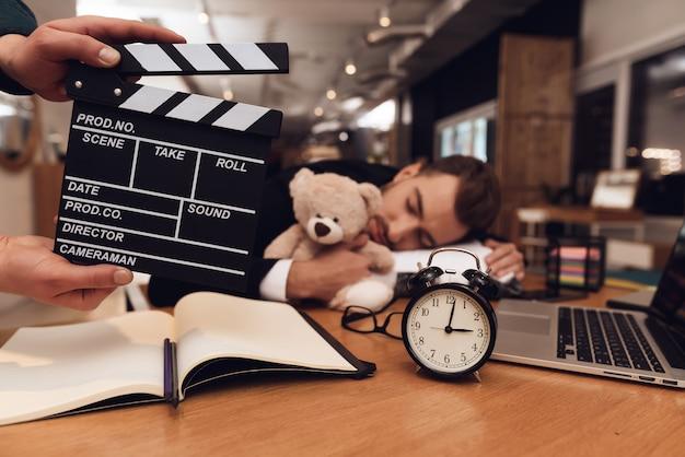 Un uomo in giacca e cravatta dorme sul posto di lavoro.