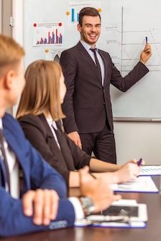 Un uomo in giacca e cravatta sta in ufficio e spiega qualcosa.