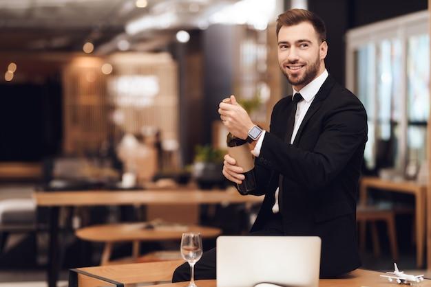 Un uomo in giacca e cravatta tiene in mano una bottiglia di vino.