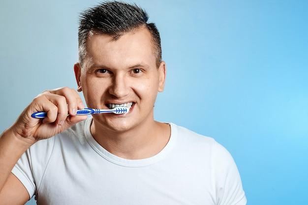 Un uomo in maglietta bianca si lava i denti sull'azzurro