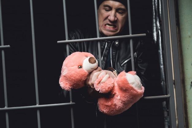 Un uomo in manette è dietro le sbarre in una stazione di polizia.