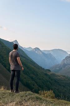 Un uomo in piedi che contempla le montagne lontane