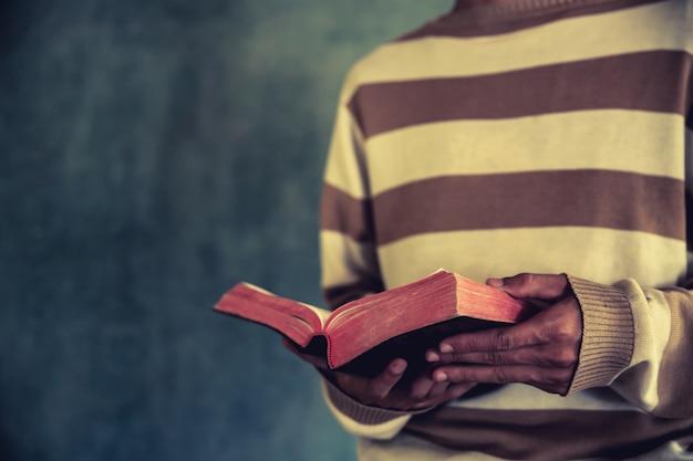 Un uomo in piedi durante la lettura della bibbia o libro sul muro di cemento con la luce della finestra