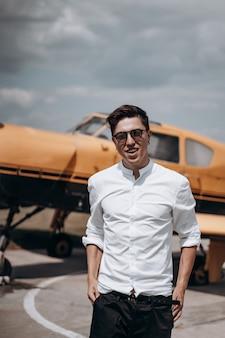 Un uomo in piedi sullo sfondo di un piccolo aereo monomotore.