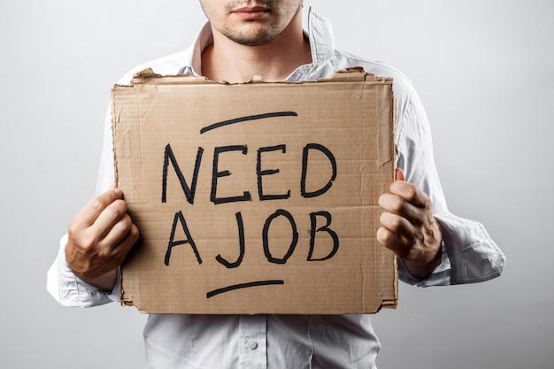 Un uomo in possesso di un cartone con un'iscrizione ha bisogno di un lavoro
