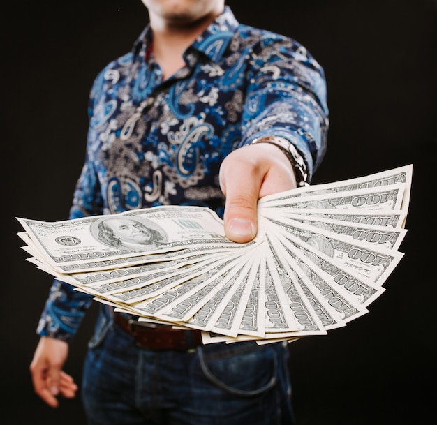 Un uomo in possesso di un fan di banconote in dollari.