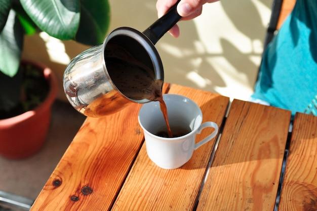 Un uomo in un caffè versa il caffè da una macchinetta del caffè in una tazza al mattino