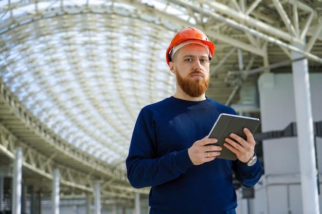 Un uomo in un casco in un grande spazio con un tablet