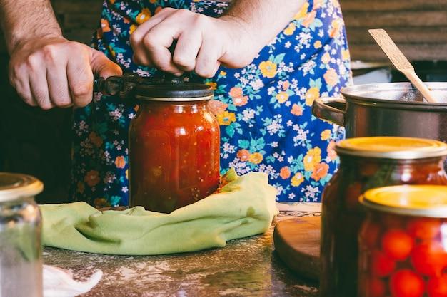 Un uomo in un grembiule colorato intasa pomodori e salsa lecho in barattoli di vetro in una casa colonica