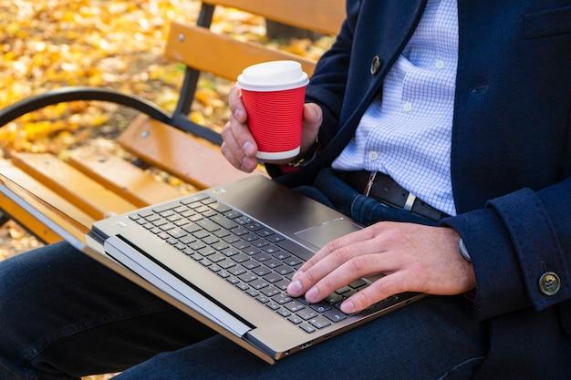 Un uomo in un parco in autunno su una panchina con un computer portatile e un caffè
