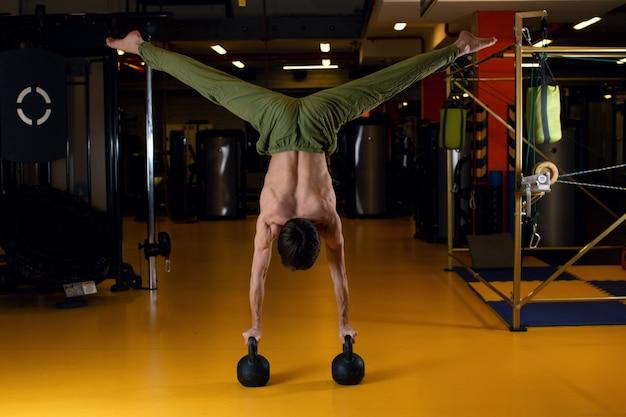 Un uomo in un rack sulle sue mani appoggiato sui pesi. acrobazia