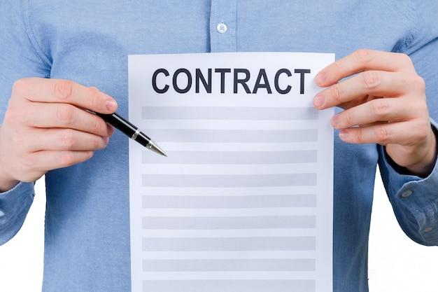 Un uomo in una camicia blu è in possesso di un foglio con un contratto e una penna su uno sfondo bianco.