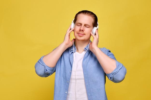 Un uomo in una camicia blu su uno sfondo giallo indossa cuffie bianche e gode della musica con gli occhi chiusi.