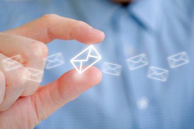 Un uomo in una camicia detiene un'icona busta astratta con la mano. il concetto di posta e il suo invio.